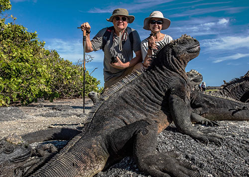 Couple with a marine iguana in the Galapagos Islands
